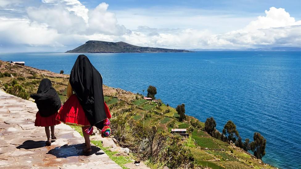 Una mujer camina junto a una niña al borde del Lago Titicaca