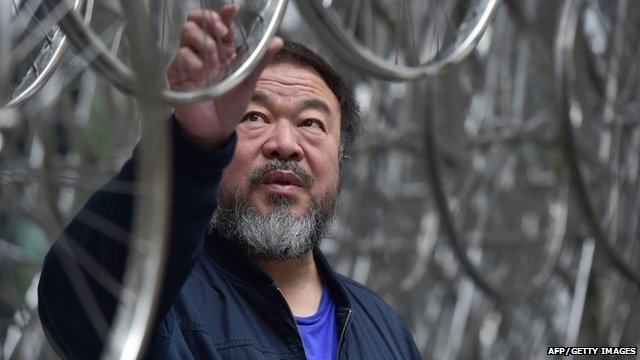 """Chinese artist Ai Weiwei touches his sculpture """"Forever"""" at the base of the the Gherkin tower"""