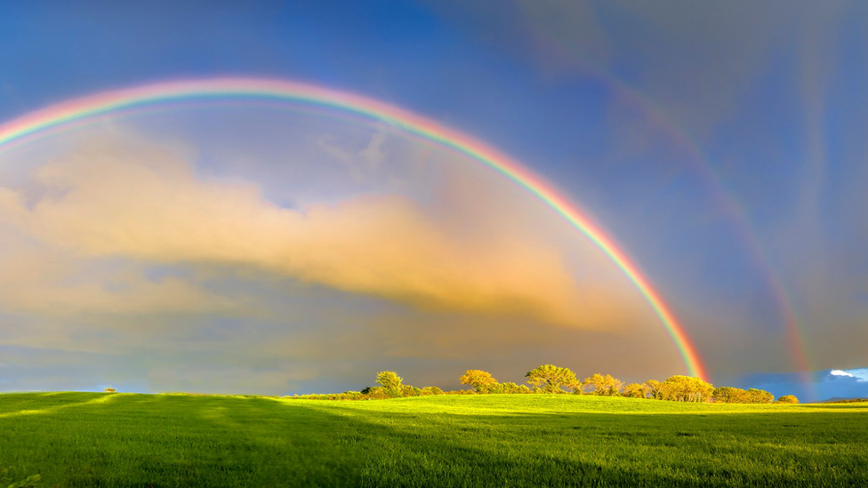 Un arcoíris doble en un cielo intensamente azul