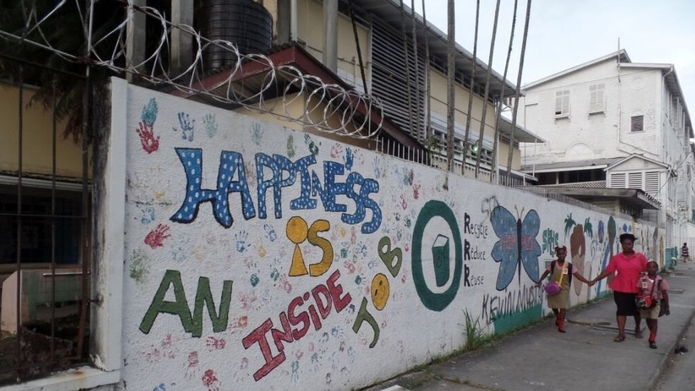 """A mural in Georgetown reads: """"Happiness is inside""""."""