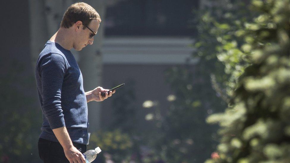 Mark Zuckerberg looks at his phone.