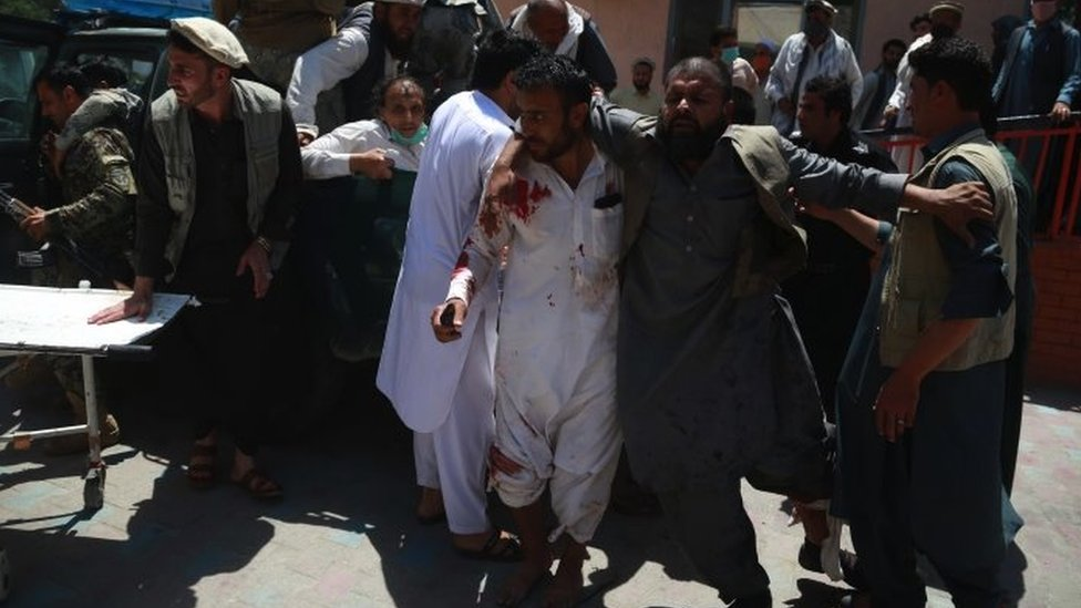 People shift injured victims of a suicide bomb attack to a hospital in Jalalabad, Afghanistan, 12 May 2020