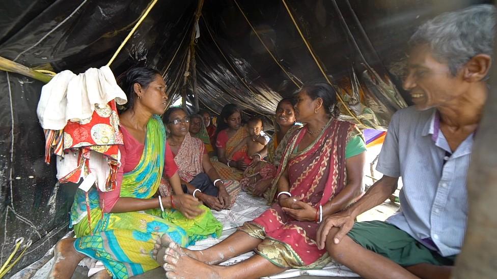 Prabhat y Phullora Mondal en una carpa con otros residentes de la isla Sonagha que perdieron su casa por las tormentas.