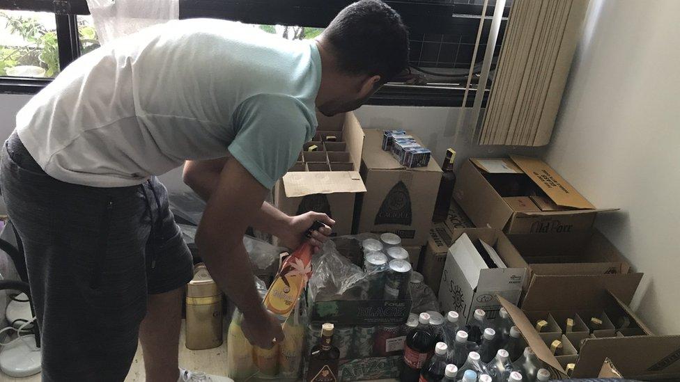 Cristian Roa recogiendo una botella de unas cajas.