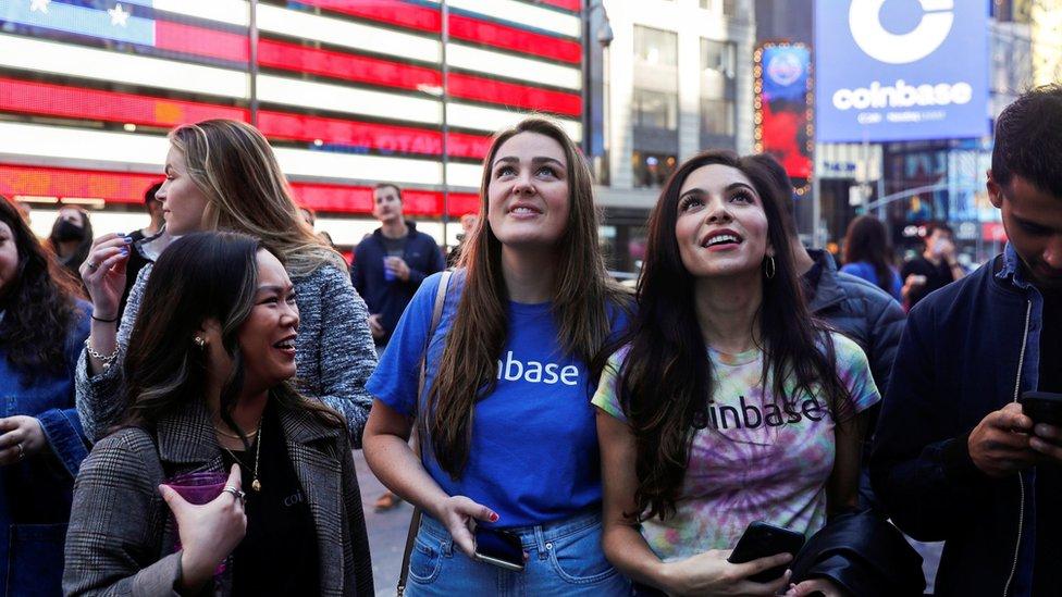 موظفو كوينبايز غلوبال، أكبر بورصة عملات رقمية في الولايات المتحدة، عرض قوائمهم على موقع سوق ناسداك في ساحة تايمز سكوير في نيويورك، الولايات المتحدة، 14 أبريل/نيسان 2021