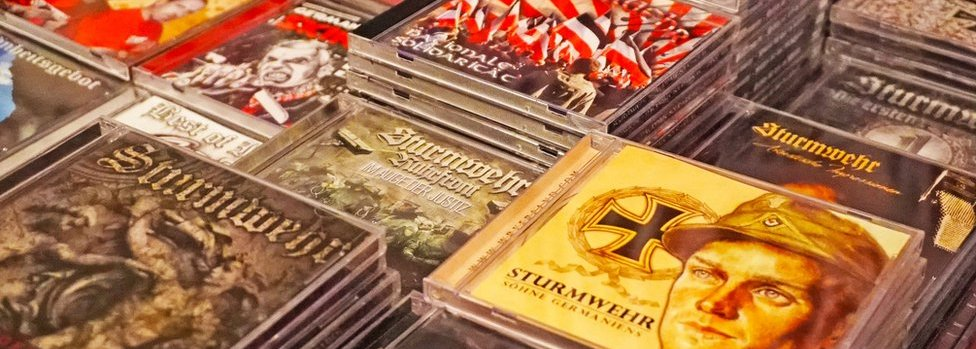 Stacks and stacks of CDs are pictured, many from the band Sturmwehr, with military images and flags visible on some cover art