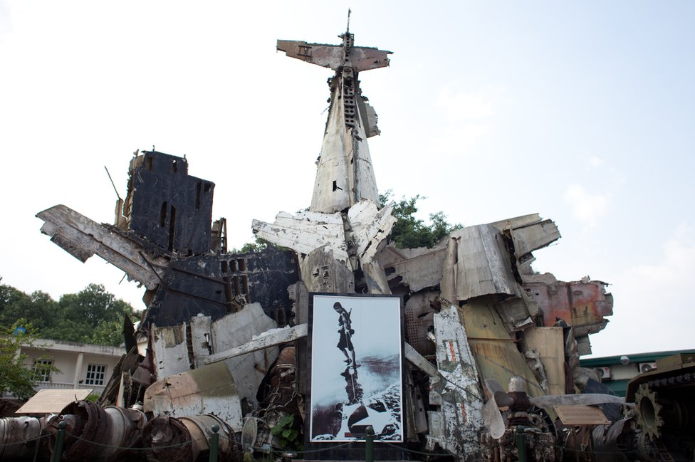 A sculpture made from wreckage of planes, with an image of a female fighter