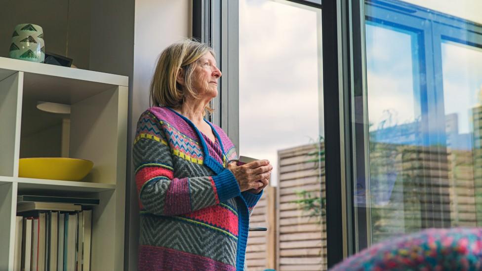 Mujer frente a una ventana