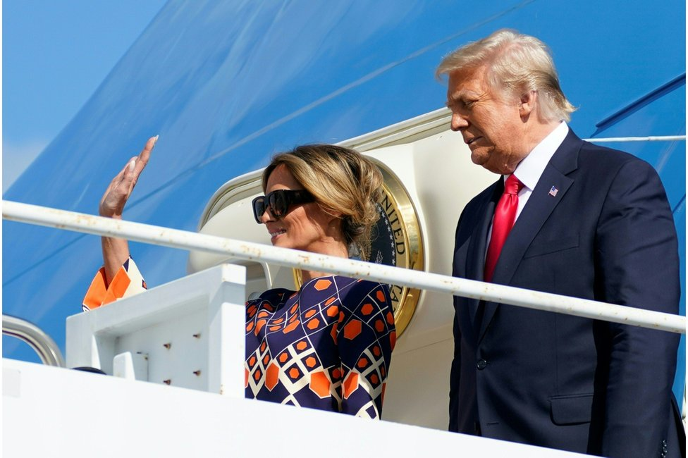 President Donald Trump and First Lady Melania Trump wave from Air Force One