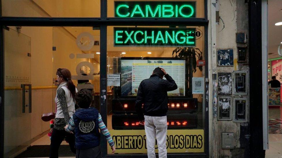 Un hombre mira la vitrina de una casa de cambios en Argentina.