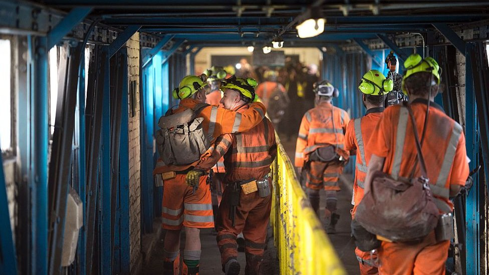 group of men in high vis walking to shift in coal mine