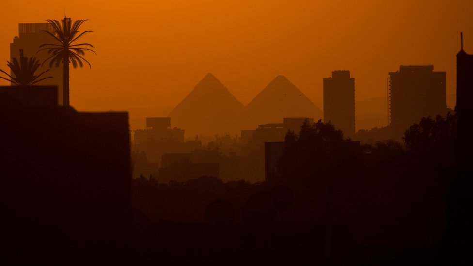 City buildings are seen in front of the famous Pyramids of Giza on 15 December 2016 in Cairo, Egypt