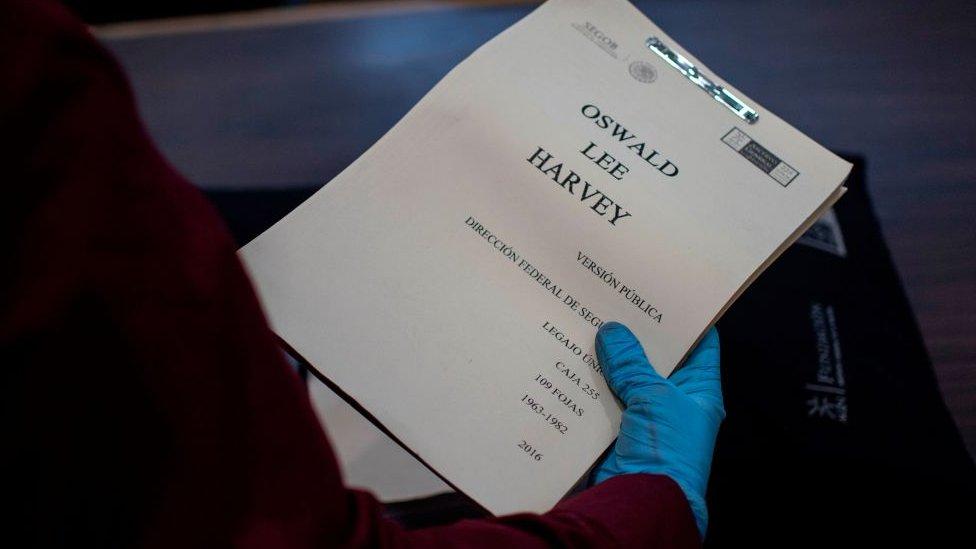 Unas manos enguantadas sostienen un reporte titulado 'Lee Harvey Oswald'