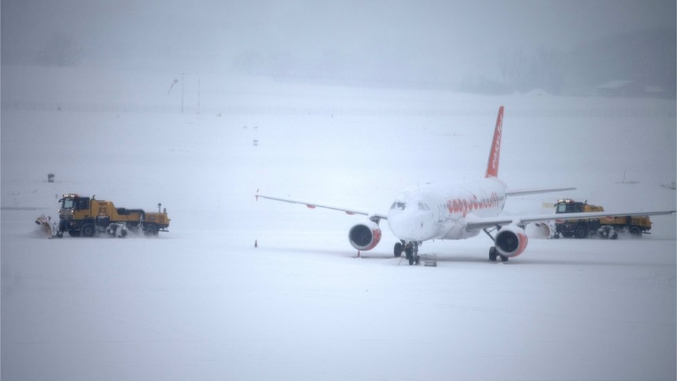 Snow plough removes snow next to an EasyJet aircraft during a temporary closure at Cointrin airport in Geneva, Switzerland, 1 March 2018