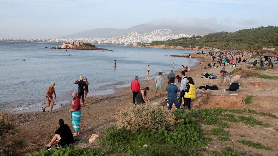 Люди наслаждаются морем на пляже недалеко от Афин, Греция, в теплый день, в то время как в выходные в стране наблюдались необычно высокие температуры.