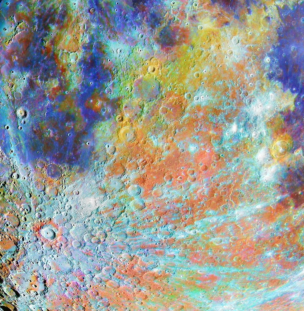 The surface of the moon showing craters with colours representing different chemical composition
