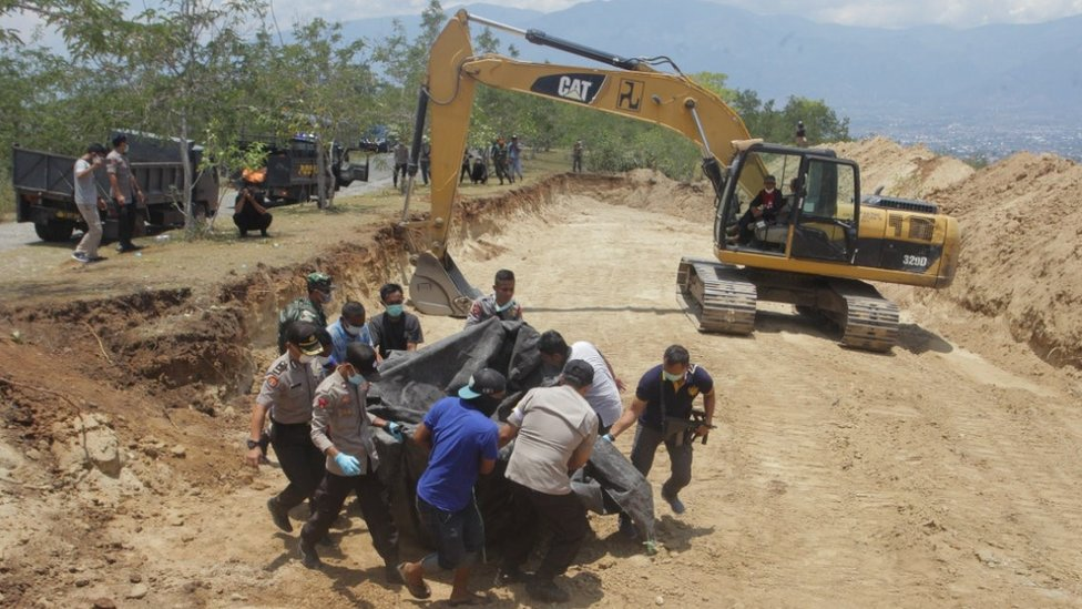 Indonesian security forces carry the body of a victim of the earthquake and tsunami into a mass grave in Palu, Central Sulawesi, Indonesia October 1, 2018