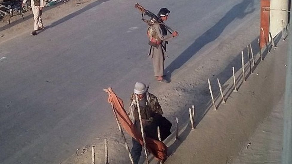 Taliban fighters walk with their weapons on a street in Kunduz, north of Kabul, Afghanistan (28 Sept 2015)