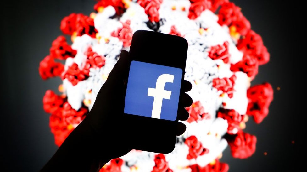 Facebook logo is displayed on a mobile phone screen photographed on SARS-CoV-2 illustration graphic background.