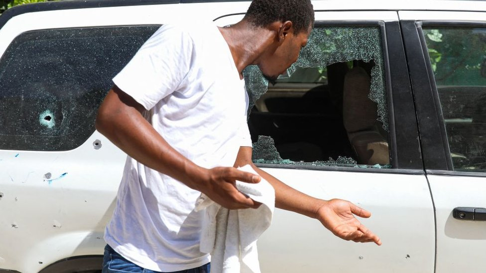 Car riddled with bullet impacts, the windows are smashed.