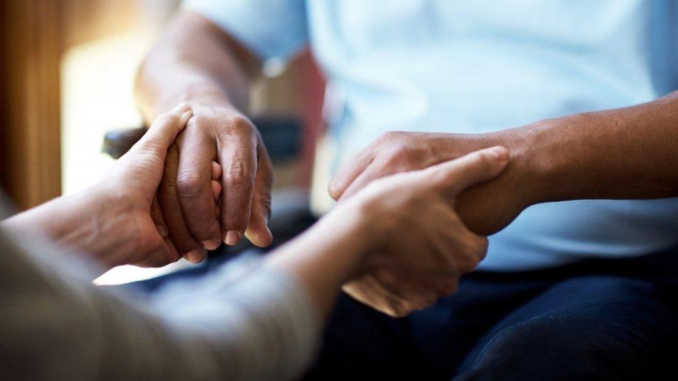 Woman holding senior man's hands