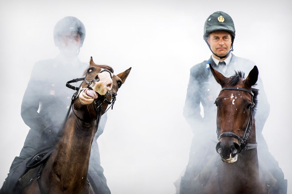 The Dutch Royal Guard guide their horses through clouds of thick smoke and gunfire on the beach of Scheveningen, near The Hague to prepare them for the Prinsjesdag parade. 16 September 2019