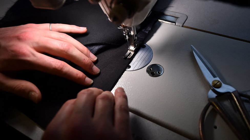 Woman sewing a seam on a garment using a sewing machine
