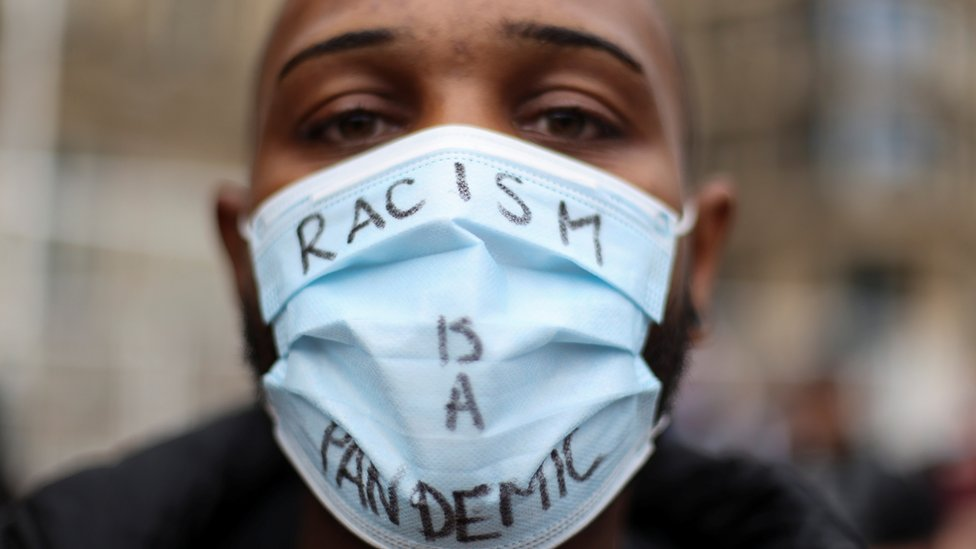 A protester wears a mask saying \