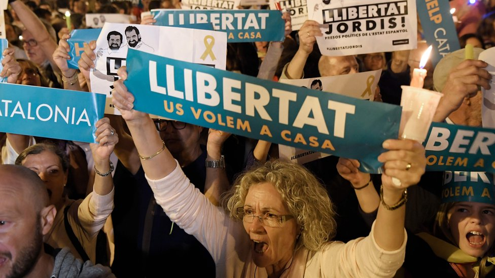 "People hold placards reading ""Freedom"" during candle-lit demonstration in Barcelona against the arrest of two Catalan separatist leaders on October 17, 2017."