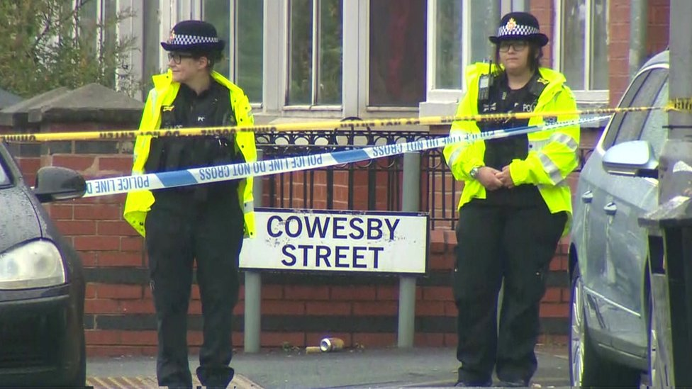 Officers standing by a sign for Cowesby Street