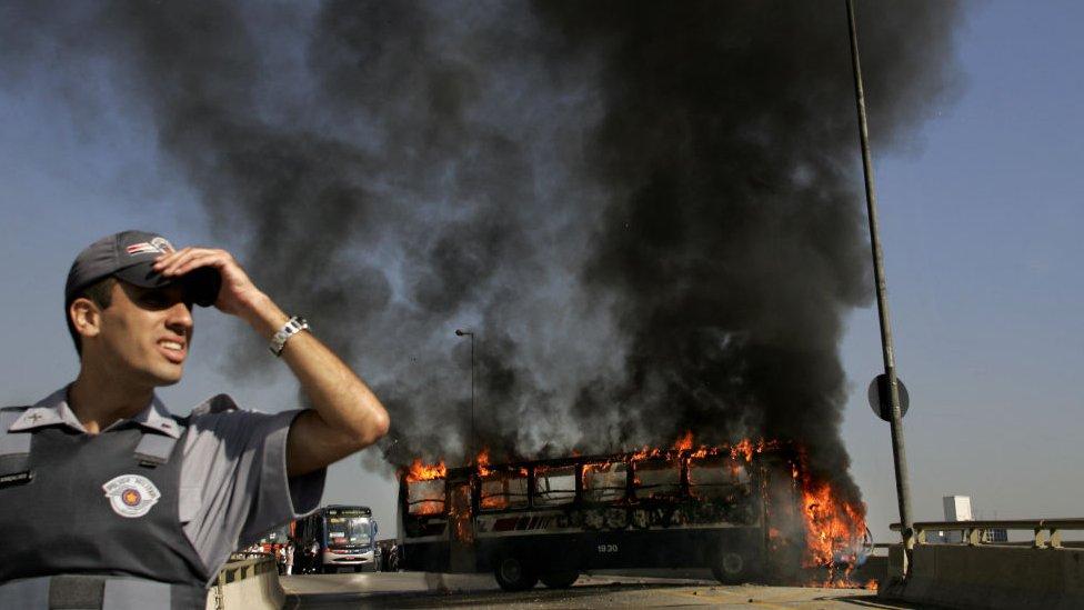 Agente de seguridad con autobús ardiendo detrás.