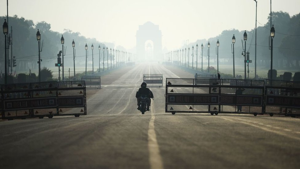 A motorist rides through deserted Rajpath road during a one-day Janata (civil) curfew imposed as a preventive measure against the COVID-19 coronavirus, in New Delhi on March 22, 2020.