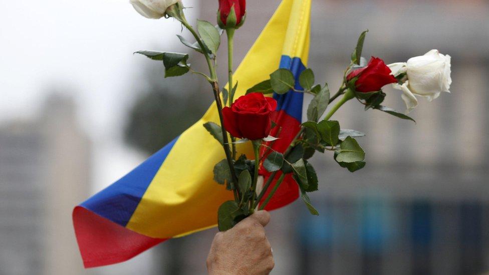 Uma senhora segura um ramo de flores com a bandeira da Colômbia