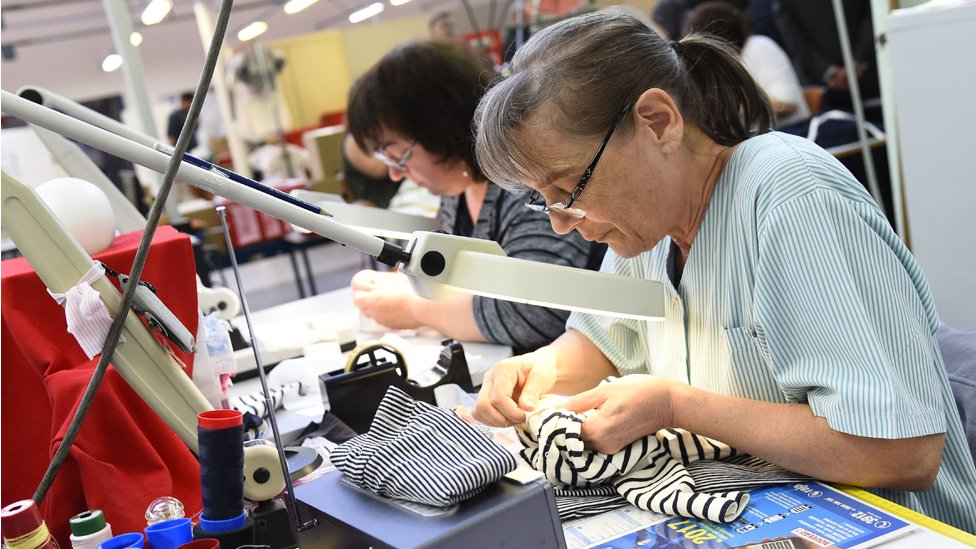 Workers sewing at French clothing firm Petit Bateau, in Troyes