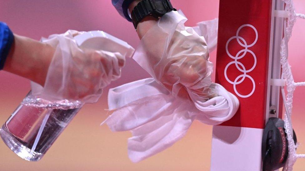 Um voluntário desinfeta o mastro de uma baliza de handebol durante uma partida nas Olimpíadas
