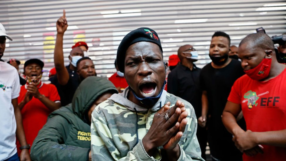 Economic Freedom Fighters (EFF) supporters chant during a picket outside a Clicks Store, at the Mall of the North in Polokwane, on September 7, 2020.