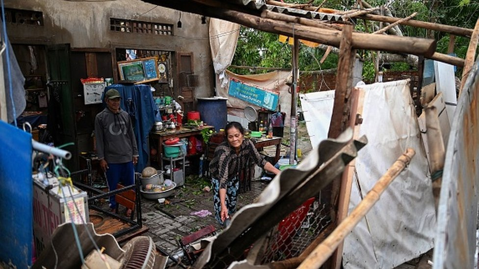 A woman clears debris from inside her house after it got damaged by the typhoon