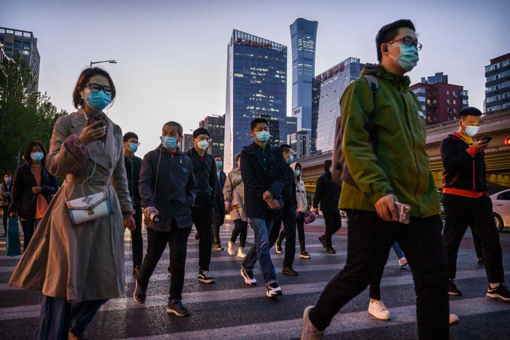 Trabajadores pendulares curzan una calle en Pekín durante la hora de alta congestión