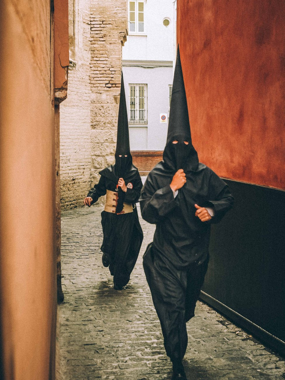Two people running to a procession in Seville