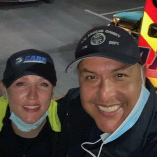 Agurcia ao lado da esposa, uma mulher branca com boné e uniforme de paramédica