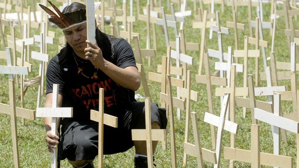 O indígena Eliseu Lopes Guarani-Kaiowá protesta em Brasília em 2012, colcoando cruzes de madeira no gramado