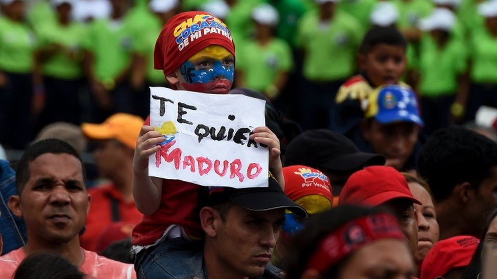 "A boy holds a sign reading ""I love you Maduro"" -referring to Venezuelan President Nicolas Maduro- during rally in Caracas on May 14,"