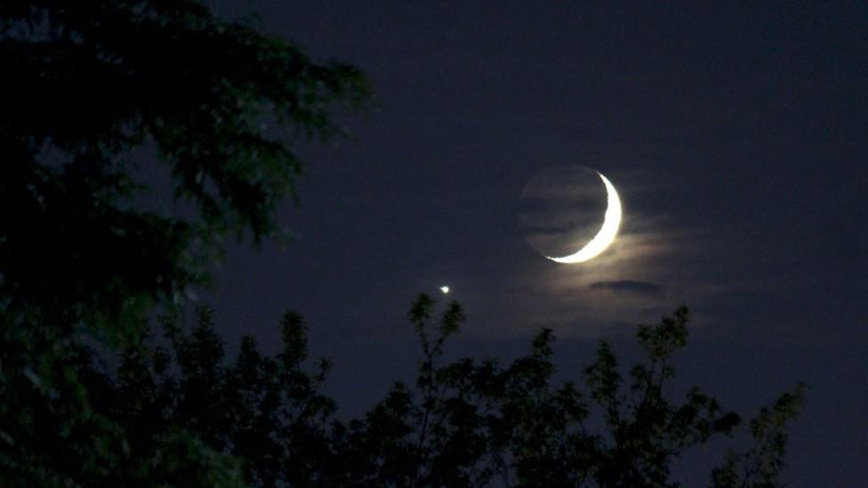 Imagen durante la noche de Venus brillante junto a la Luna creciente