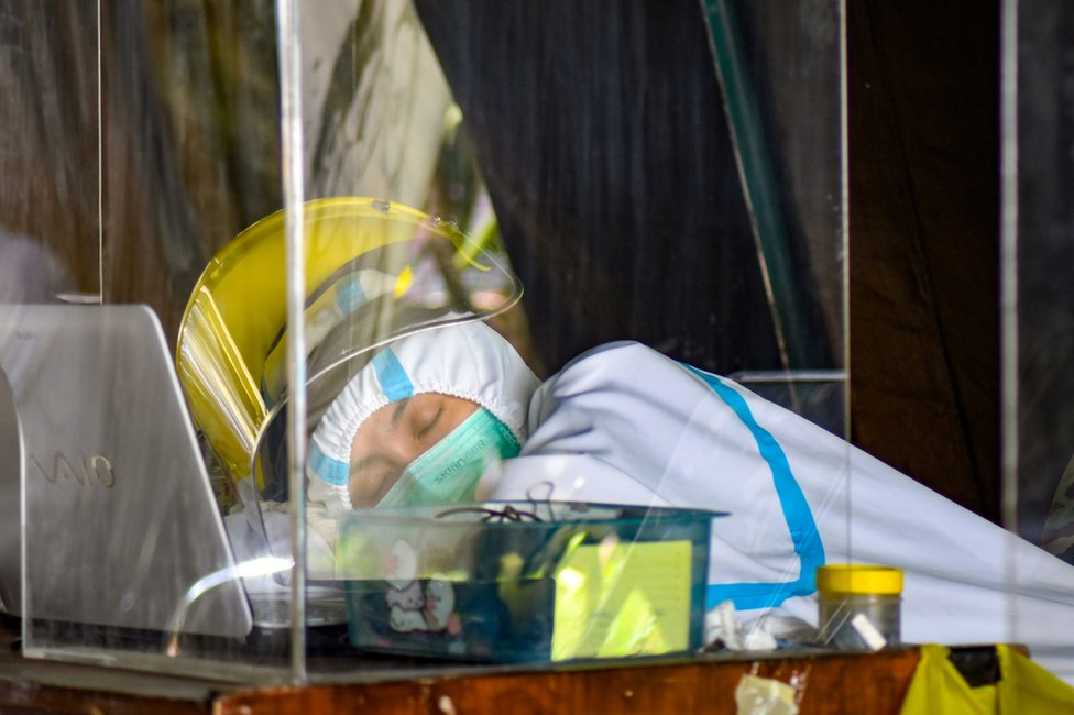 A health worker leans on a table whilst sleeping