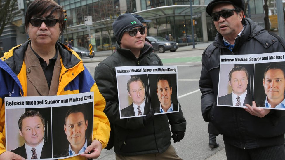 Protesters hold signs calling for the release of Michael Spavor and Michael Kovrig