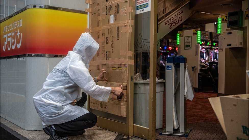 A man covers over a doorway to a pachinko parlour ahead of the arrival of Typhoon Hagibis on October 12, 2019 in Tokyo, Japan
