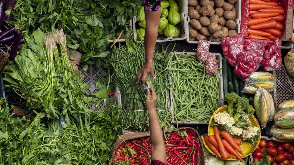 La mano de una mujer alcanza una bolsa con alimentos a otra, con un surtido de frutas y verduras en el fondo.