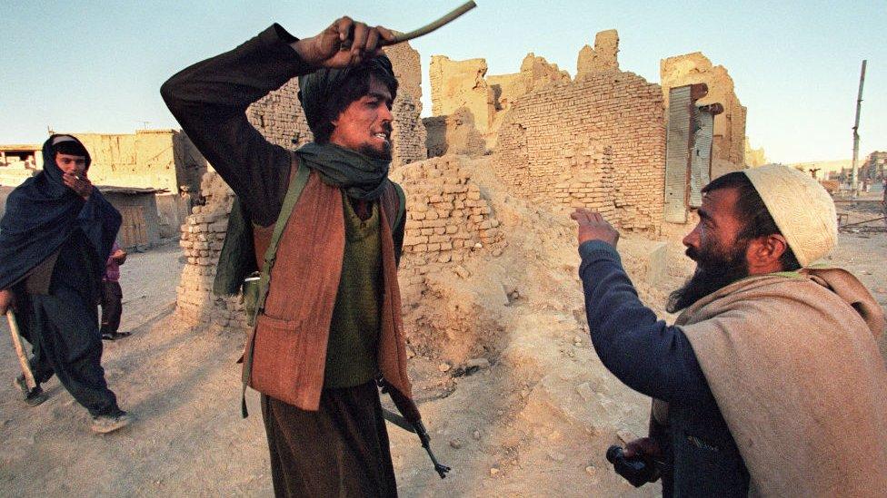 Un combatiente talibán castigando a otro hombre en Afganistán.