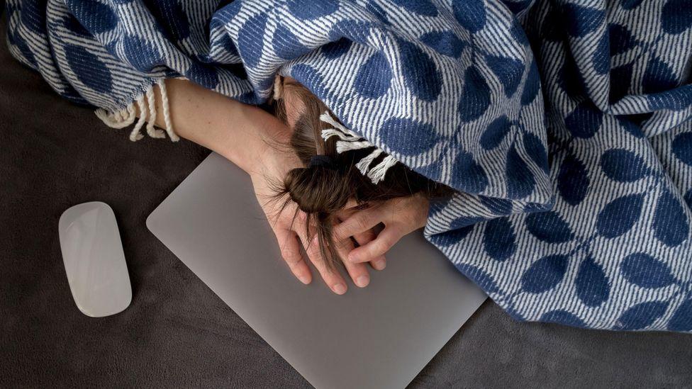 Mulher deitada com a cabeça em cima do laptop