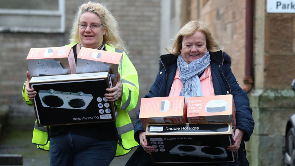 People leave Camelon community centre in Falkirk with hot plates and fan heaters